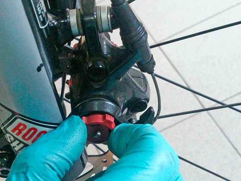 10. Вкручивая левый винт регулировки подвижной колодки, подведите её максимально близко к ротору.