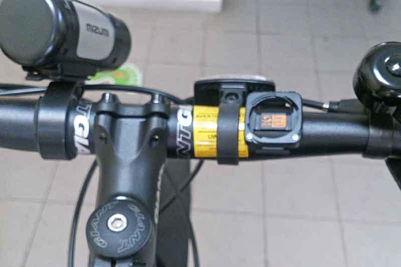 2. Прикрепите базу на руль или вынос (как вам удобно) двумя контактами вниз, и закрепите её резинкой меньшего диаметра.